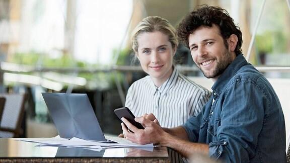 Ein Paar sitzt lachend mit Smartphone vor einem Laptop.