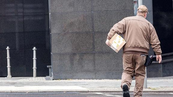 Paketbote der Firma UPS bei der Lieferung eines Paketes.