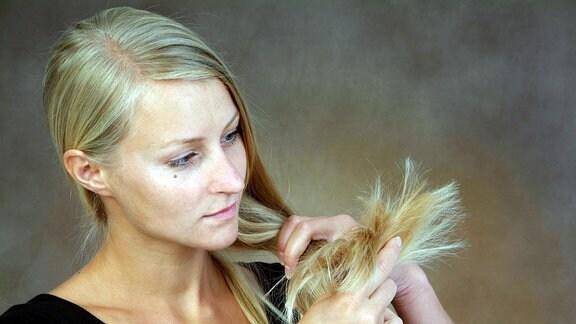 Eine Frau schaut auf ihre Haarspitzen