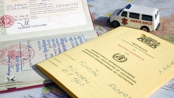 Impfausweis, Pass und Krankenwagen auf einer Landkarte.