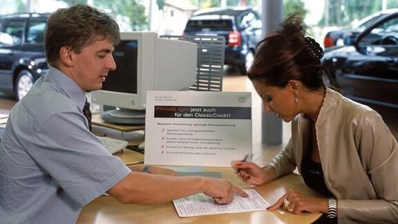 Junge Frau unterschreibt 2001 einen Vertrag im Autohaus
