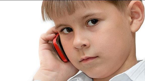 Ein Kind telefoniert mit einem Handy.