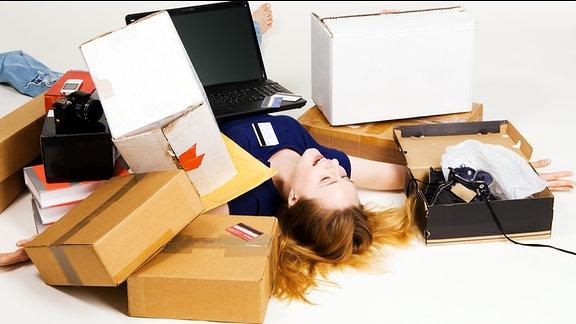 Eine junge Frau liegt rücklings auf dem Boden. Auf ihrem Bauch liegt ein Laptop. Um sie herum liegen Bücher, diverse Pakete und andere Artikel