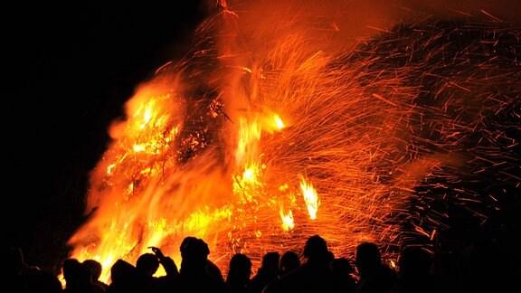 Bei Nacht stehen Menschen gemeinsam vor einem Osterfeuer.