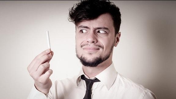 Geschäftmann blickt mit verzerrtem Gesicht auf Zigarette in seiner Hand