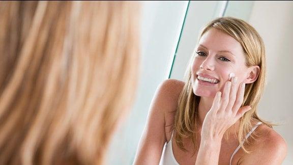 Eine Frau crmet sich vor dem Spiegel das Gesicht ein.