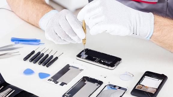 Behandschuhte Hände reparieren ein Handy.