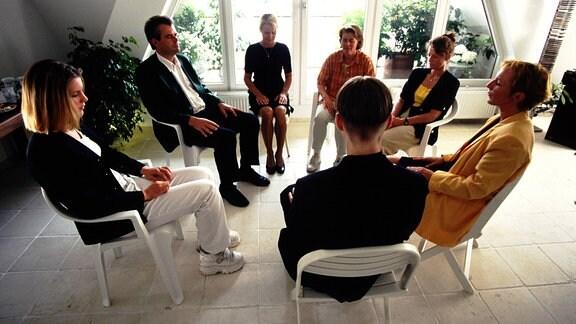 Menschen sitzen in einem Gesprächskreis zusammen.