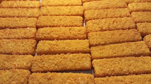 Fischstäbchen im Ofen auf einem Ofenblech.