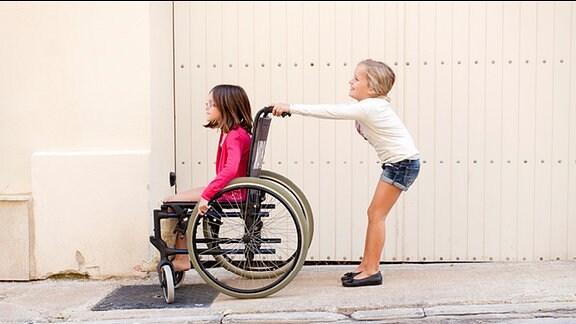 Ein Mädchen schiebt ein anderes Mädchen, das im Rollstuhl sitzt.