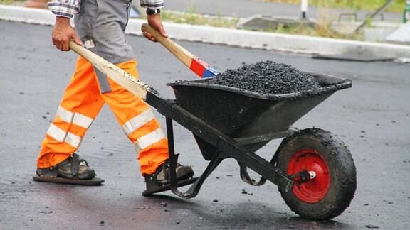 Bauarbeiter schiebt Schubkarre