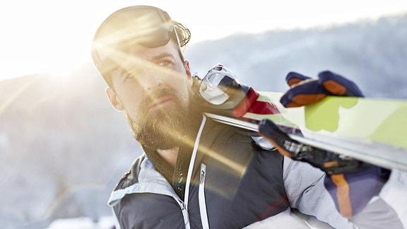 Ein Mann trägt ein Paar Ski auf der Schulter