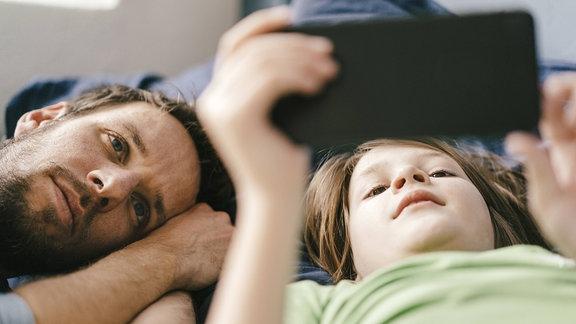 Vater und Sohn schauen zusammen auf ein Smartphone
