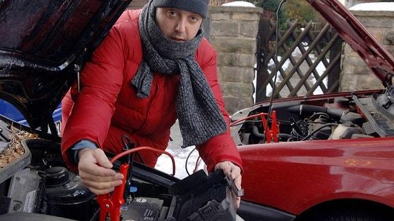 Mann befestigt ein Überbrückungskabel an der Autobatterie eines hilfsbereiten Autofahrers