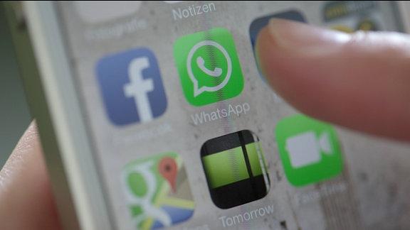Finger weist auf ein WhatsApp-Icon auf einem Smartphone-Display