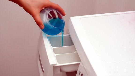 Flüssigwaschmittel wird in eine Waschmaschine gegeben