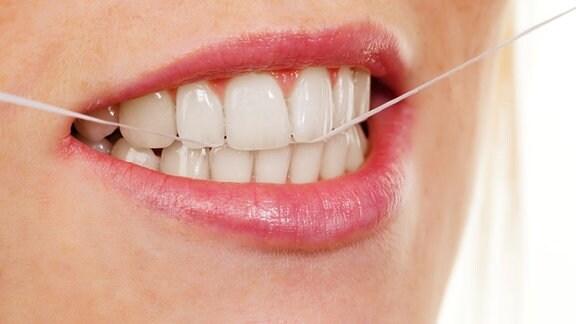 Nahaufnahme eines Gebisses mit Zahnseide.