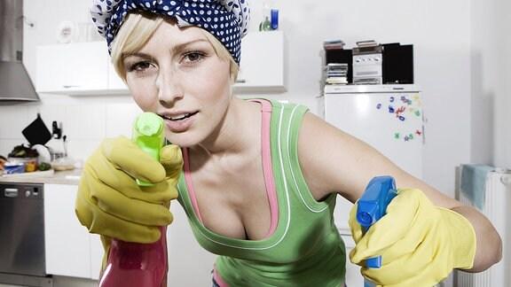 Eine junge Frau mit Gummihandschuhen hält in jeder Hand eine Flasche mit Reinigungsmitteln.