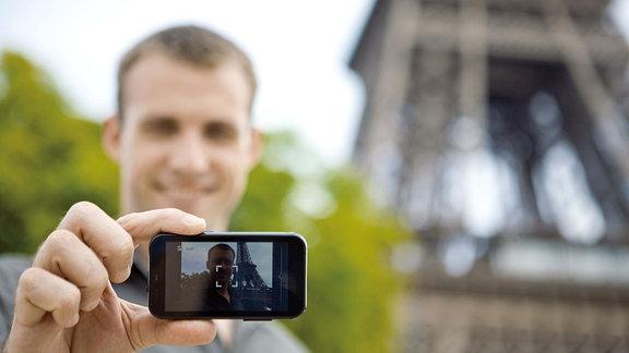 Ein Mann fotografiert sich mit dem Smartphone vor dem Eiffelturm in Paris.
