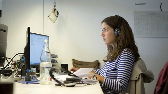 Eine junge Frau sitzt an einem Computerarbeitsplatz.