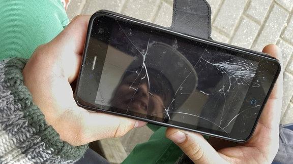 Eine Hand hält ein Smartphone mit gesprungenem Display.