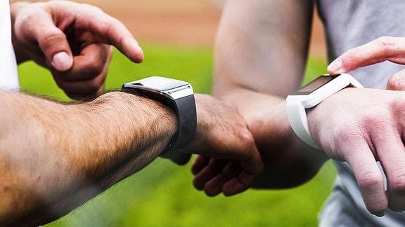 Zwei Sportler zeigen sich ihre Smartwatches.
