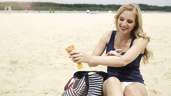 Eine Frau reibt sich mit Sonnencreme am Strand ein.