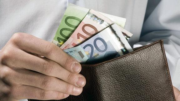 Ein Mann zieht Geldscheine aus einem Portemonnaie.