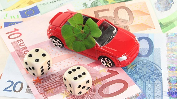 Ein rotes Spielzeugauto mit einem vierblättrigen Kleeblatt steht auf Geldscheinen, daneben zwei Würfel.