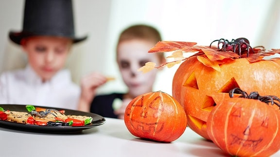 Zwei verkleidete Kinder und Halloween-Kürbisse