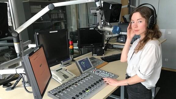 Junge Frau mit Kopfhörer steht vor einem Mischpult und Computerbildschirmen