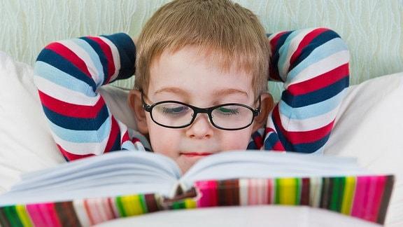 Ein Junge liegt im Bett und liest