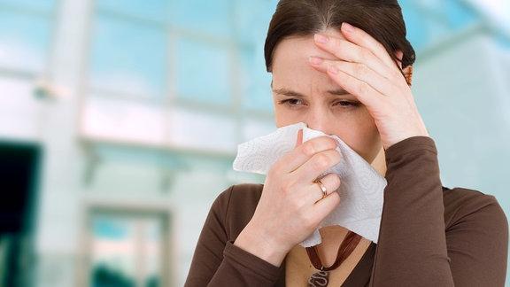Frau hält sich ein Taschentuch an die Nase und greift mit einer Hand an ihre Stirn