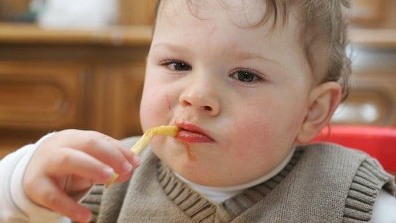 Dickes Kleinkind isst Pommes.