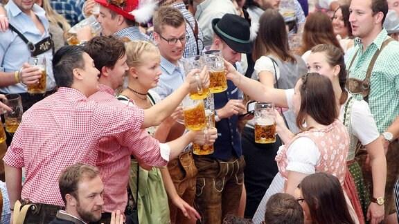 Ausgelassen feiernde junge Leute stoßen gemeinsam mit einer Maߟ Bier an.