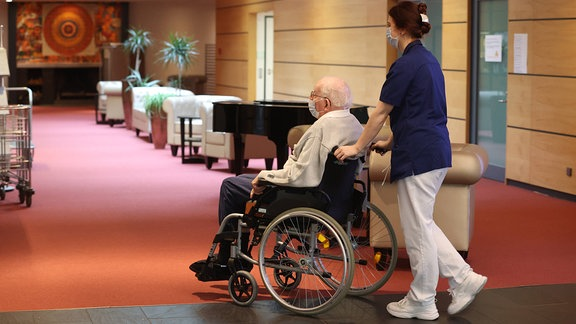 Eine Pflegerin schiebt einen Mann in einem Rollstuhl. Beide tragen einen Mundschutz.