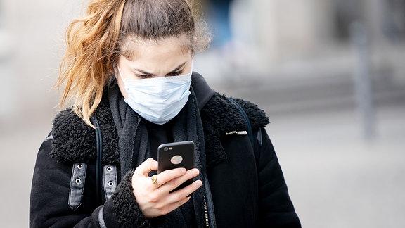 Eine Frau blickt auf ihr Smartphone.