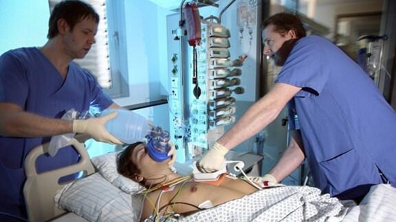Patient wird von Hand beatmet, Reanimation durch Elektroschock wird vorbereitet, mit einem Defibrillator.