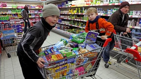 Kinder mit vollem Einkaufswagen in einer Lebensmittelabteilung