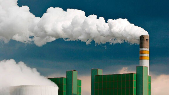 Qualmender Schornstein gegen bedrohlichen dunklen Himmel, Braunkohlekraftwerk, Kraftwerk Schkopau.