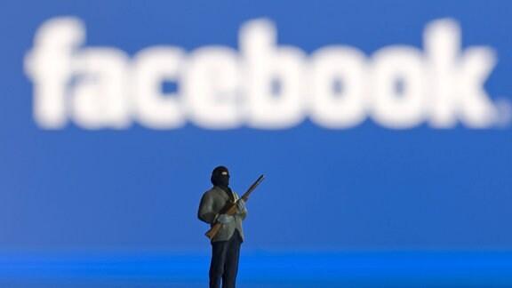 Miniaturfigur vor unscharfem Facebook-Logo