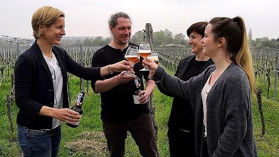 Menschen stehen im Weinberg und trinken Bier
