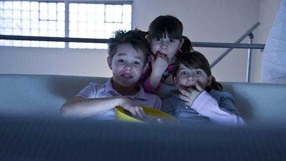Kinder schauen einen Film und Naschen