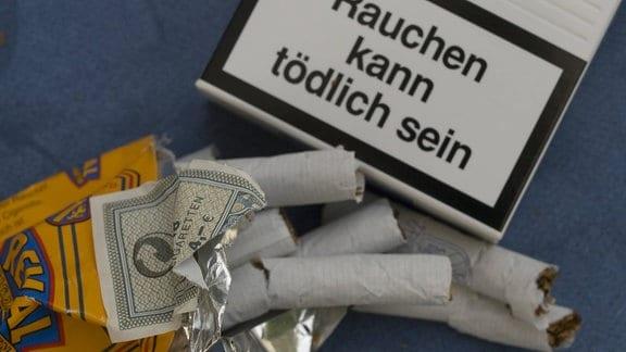 Zerknüllte Packung filterlose Reval-Zigaretten neben dem Warnhinweis einer anderen Zigarettenschachtel