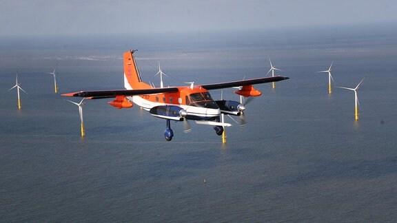 Das Forschungsflugzeug der TU Braunschweig über der Nordsee vor einem Windpark
