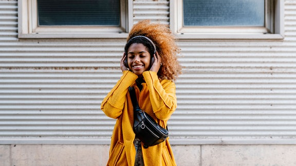 Junge Frau mit langen, lockigen Haaren und gelbem Mantel steht vor einer Hauswand und hört Musik mit Kopfhörern, hält Kopfhörer mit den Händen, freudiger Gesichtsausdruck