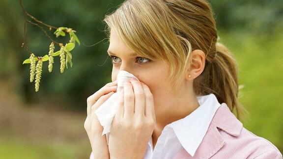 Eine Frau putzt sich neben Birkenpollen die Nase