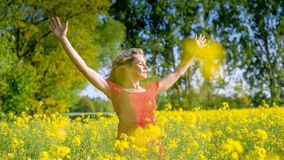 Frau in rotem Kleid und längeren, blonden, gewellten Haaren steht mit erhobenen Armen und verschlossenen Augen inmitten eines blühenden Rapsfeldes. Im Vordergrung unscharf einige Rapsblüten vor der Kamera, im Hintergrund Bäume.