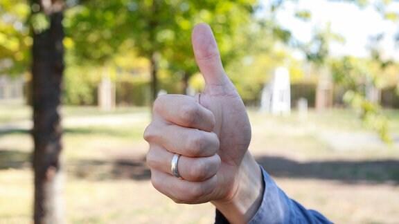 Eine Hand streckt einen Daumen nach oben