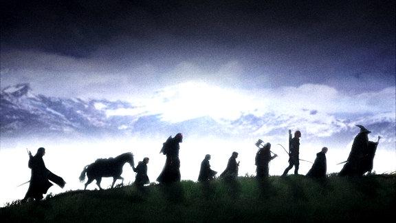 """Die Gemeinschaft des Rings aus """"Der Herr der Ringe - Die Gefährten"""" läuft über einen Bergkamm."""